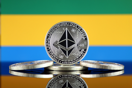 Physical version of Ethereum (ETH) and Gabon Flag. Conceptual image for investors in cryptocurrency, Blockchain Technology, Smart Contracts, Personal Tokens and Initial Coin Offering.