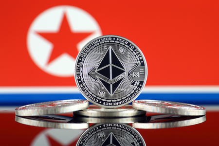 Physical version of Ethereum (ETH) and North Korea Flag. Conceptual image for investors in cryptocurrency, Blockchain Technology, Smart Contracts, Personal Tokens and Initial Coin Offering. Stock Photo