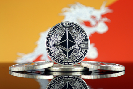 Physical version of Ethereum (ETH) and Bhutan Flag. Conceptual image for investors in cryptocurrency, Blockchain Technology, Smart Contracts, Personal Tokens and Initial Coin Offering.