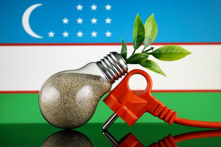Plug, plant growing inside the light bulb and Uzbekistan Flag. Green eco renewable energy concept. Stock fotó