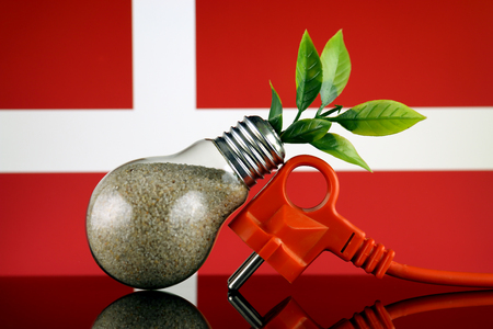 Plug, plant growing inside the light bulb and Denmark Flag. Green eco renewable energy concept.