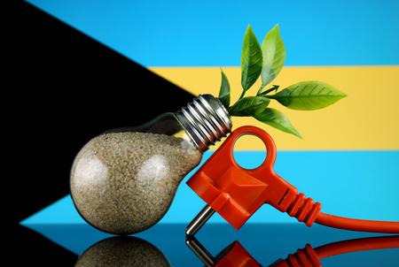 Plug, plant growing inside the light bulb and Bahamas Flag. Green eco renewable energy concept.
