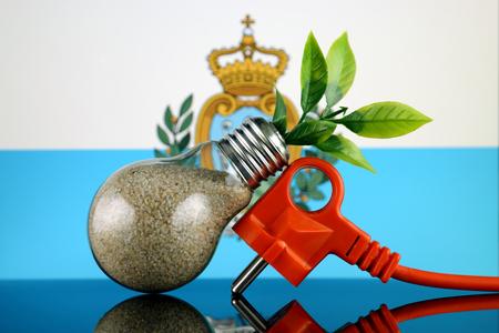 Plug, plant growing inside the light bulb and San Marino Flag. Green eco renewable energy concept.