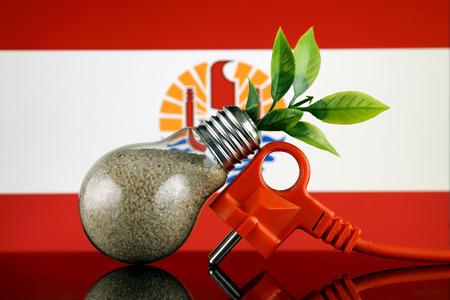 Plug, plant growing inside the light bulb and French Polynesia Flag. Green eco renewable energy concept.