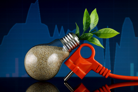 Plug and plant growing inside the light bulb. Green eco renewable energy concept. Electricity prices, energy saving.