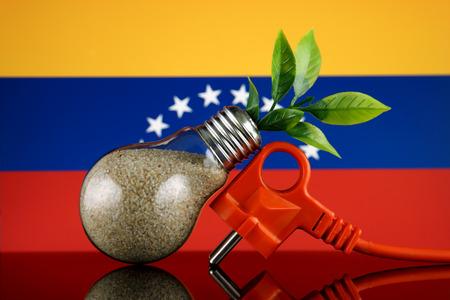 Plug, plant growing inside the light bulb and Venezuela Flag. Green eco renewable energy concept.