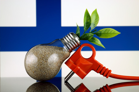 Plug, plant growing inside the light bulb and Finland Flag. Green eco renewable energy concept.