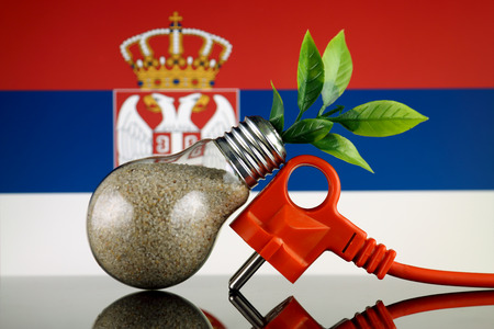 Plug, plant growing inside the light bulb and Serbia Flag. Green eco renewable energy concept. Stockfoto