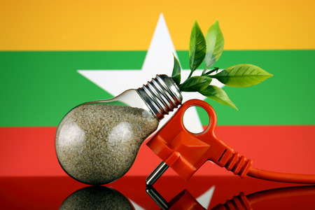 Plug, plant growing inside the light bulb and Myanmar Flag. Green eco renewable energy concept. Stock fotó