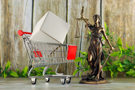Shopping trolley and symbol of law and justice. Consumer rights concept. Regulations, restrictions, prohibition. Stok Fotoğraf