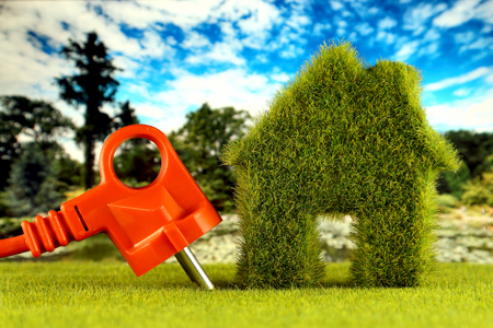 Plug and green eco house icon concept with grass and blue sky background. Renewable energy. Electricity prices, energy saving in the household.