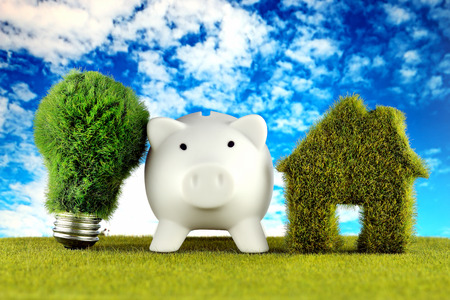 Piggy bank, green eco light bulb and eco house icon concept with grass and blue sky background. Renewable energy. Electricity prices, energy saving in the household. Imagens