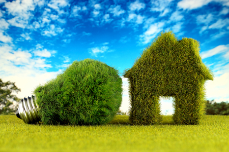 Green eco light bulb and eco house icon concept with grass and blue sky background. Renewable energy. Electricity prices, energy saving in the household.