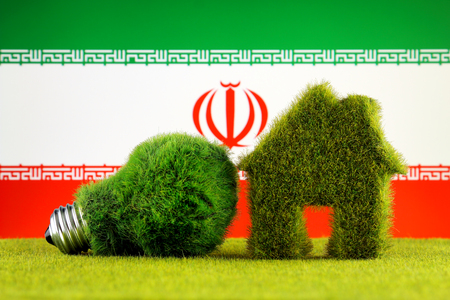 Green eco light bulb, eco house icon and Iran Flag. Renewable energy. Electricity prices, energy saving in the household. Stock Photo