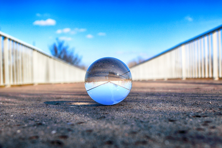 Long bridge in Wroclaw, Poland. View through a glass, crystal ball (lensball) for refraction photography. Stockfoto