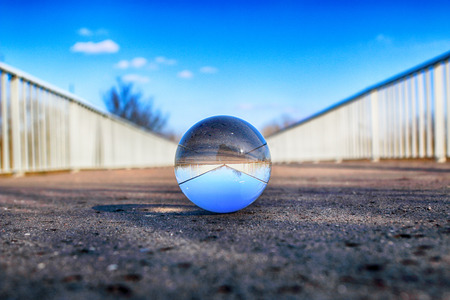 Long bridge in Wroclaw, Poland. View through a glass, crystal ball (lensball) for refraction photography. 스톡 콘텐츠