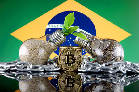 Bitcoin (BTC), green renewable energy concept, and Brazil Flag. Electricity prices, energy saving in the cryptocurrency mining business. Imagens