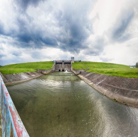The water dam on Mietkow Lake (near Wroclaw, Poland) in the last days of May. Beautiful storm clouds and sunbeams.