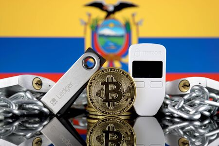 WROCLAW, POLAND - JULY 06, 2019: Physical version of Bitcoin (BTC), Trezor and Ledger (cryptocurrency hardware wallets), padlocks, chain (like Blockchain Technology) and Ecuador Flag.