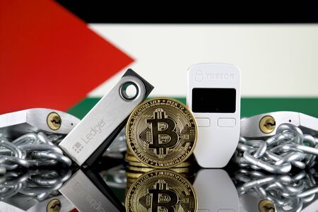 WROCLAW, POLAND - JULY 06, 2019: Physical version of Bitcoin (BTC), Trezor and Ledger (cryptocurrency hardware wallets), padlocks, chain (like Blockchain Technology) and Palestine Flag. 報道画像