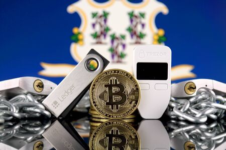 WROCLAW, POLAND - JULY 06, 2019: Physical version of Bitcoin (BTC), Trezor and Ledger (cryptocurrency hardware wallets), padlocks, chain (like Blockchain Technology) and Connecticut State Flag. Editorial