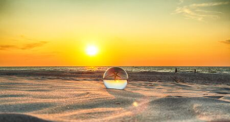 Beautiful sunset on the beach  View through a glass, crystal ball (lensball) for refraction photography. Wild, untouched nature.