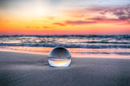 Beautiful sunset on the beach in Slowinski National Park near Leba, Poland. View through a glass, crystal ball (lensball) for refraction photography. Wild, untouched nature. Фото со стока