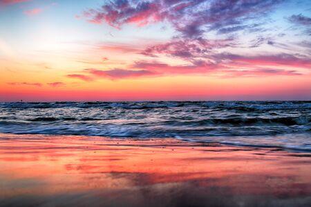 Baltic Sea and beautiful sunset on the beach in Slowinski National Park near Leba, Poland. Wild, untouched nature. Фото со стока