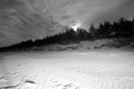 Slowinski National Park on the Baltic Sea coast, near Leba, Poland. Night view, starry sky right after the moon rising. Beautiful sandy beaches and coastal landscape.