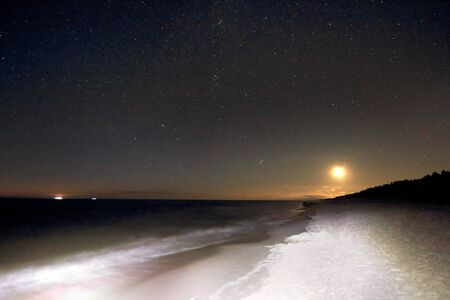 Slowinski National Park on the Baltic Sea coast, near Leba, Poland. Night view, starry sky right after the moon rising. Beautiful sandy beaches and coastal landscape. 版權商用圖片