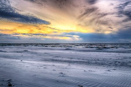 Baltic Sea and beautiful sunset on the beach in Slowinski National Park near Leba, Poland. Wild, untouched nature. 免版税图像