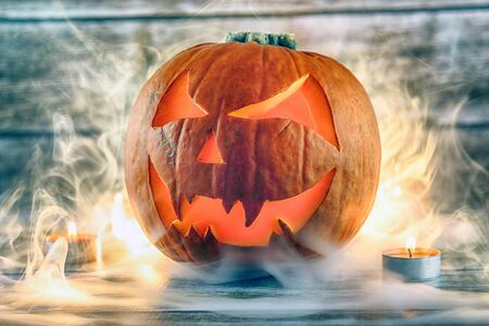 Halloween pumpkin with smoke and candles on wooden background. Studio shot. Stock Photo
