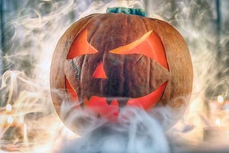 Halloween pumpkin with smoke and candles on wooden background.