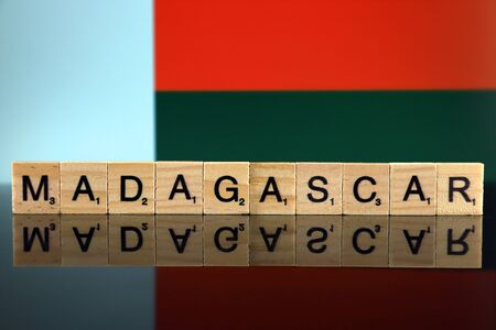 Madagascar Flag and country name made of small wooden letters. Studio shot. Фото со стока