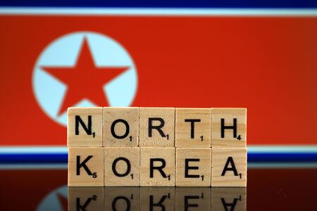 North Korea Flag and country name made of small wooden letters. Studio shot.