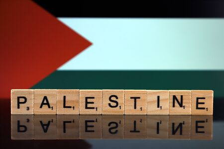Palestine Flag and country name made of small wooden letters. Studio shot.