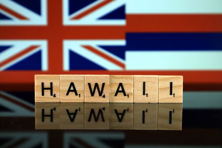 Hawaii Flag and state name made of small wooden letters. Studio shot.