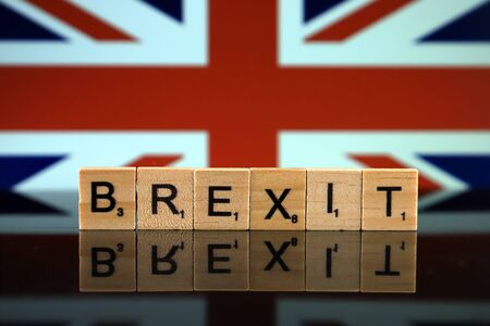 United Kingdom Flag and word BREXIT made of small wooden letters. Studio shot.