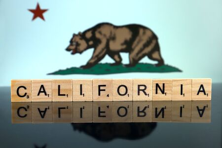 California State Flag and state name made of small wooden letters. Studio shot.