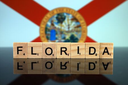Florida State Flag and state name made of small wooden letters. Studio shot.