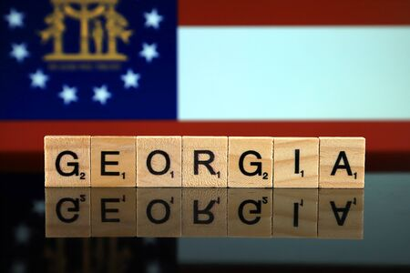 Georgia State Flag and state name made of small wooden letters. Studio shot.