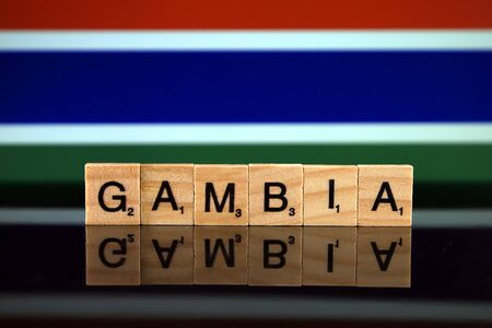 Gambia Flag and country name made of small wooden letters. Studio shot.