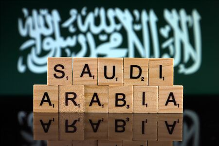 Saudi Arabia Flag and country name made of small wooden letters. Studio shot.