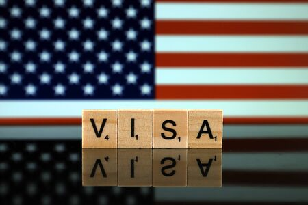 United States Flag and word VISA made of small wooden letters. The visa policy of the United States