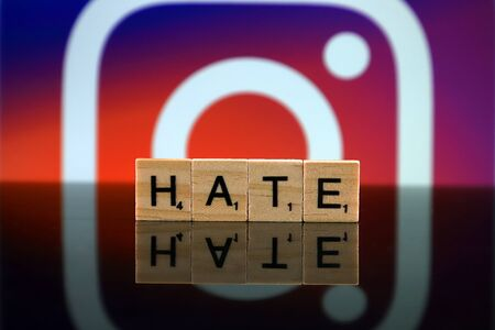 WROCLAW, POLAND - FEBRUARY 12, 2020: Word HATE made of small wooden letters, and INSTAGRAM logo in the background. Studio shot.