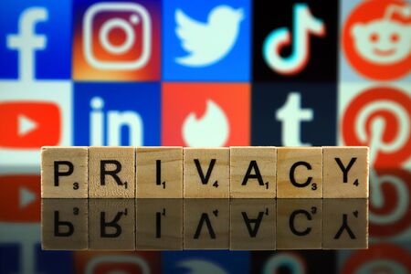 WROCLAW, POLAND - FEBRUARY 12, 2020: Word PRIVACY made of small wooden letters, and FACEBOOK, INSTAGRAM, TWITTER, TIK TOK, REDDIT, YOUTUBE, LINKEDIN, TINDER, TUMBLR, PINTEREST logos in the background