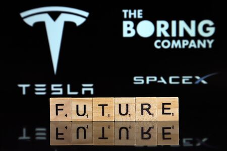 WROCLAW, POLAND - FEBRUARY 19, 2020: Word FUTURE made of wooden letters, and TESLA, SPACEX, THE BORING COMPANY logos in the background.