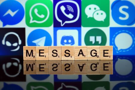 WROCLAW, POLAND - FEBRUARY 19, 2020: Word MESSAGE made of wooden letters, and MESSENGER, WHATSAPP, VIBER, WECHAT, SKYPE, TEAMSPEAK, TELEGRAM, DISCORD, GOOGLE HANGOUTS, SIGNAL logos in the background.
