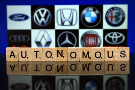 WROCLAW, POLAND - FEBRUARY 19, 2020: Word AUTONOMOUS made of wooden letters, and FORD, VOLKSWAGEN, HONDA, BMW, ALFA ROMEO, AUDI, RENAULT, MERCEDES, FIAT, TOYOTA logos in the background.