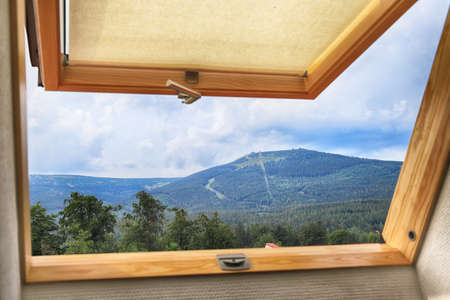 Open roof window, skylight with beautiful mountain view.